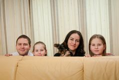 Family portrait at home. Behind sofa - with two children and dog Royalty Free Stock Photos
