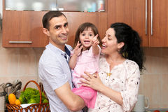 Family portrait in kitchen interior with fresh fruits and vegetables, healthy food concept, pregnant woman, man and child girl Royalty Free Stock Photography