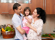 Family portrait in kitchen interior with fresh fruits and vegetables, healthy food concept, pregnant woman, man and child girl Stock Photo