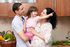 Family portrait in kitchen interior with fresh fruits and vegetables, healthy food concept, pregnant woman, man and child girl Royalty Free Stock Photos