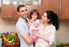 Family portrait in kitchen interior with fresh fruits and vegetables, healthy food concept, pregnant woman, man and child girl royalty free stock images