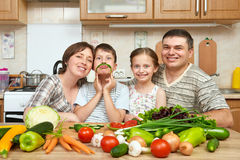 Family portrait in kitchen interior at home, fresh fruits and vegetables, healthy food concept, woman, man and children cooking an Stock Image
