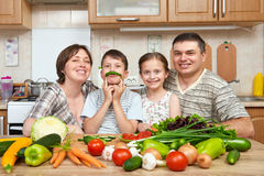 Family portrait in kitchen interior at home, fresh fruits and vegetables, healthy food concept, woman, man and children cooking an Stock Photo