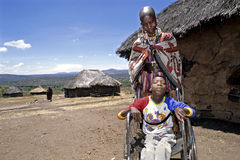 Family portrait of Maasai mother and disabled son. Kenya, village Entesekera: Group portrait of the handicapped boy with mother for house, mud hut, house in Stock Photo