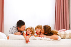 Family portrait of mom dad and daughters on bed Stock Photography