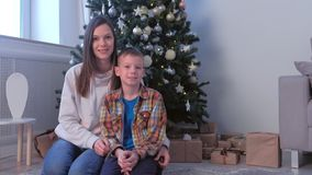 Family portrait of mom and son sitting smiling near Christmas tree at home. Family portrait of mom and son sitting near Christmas tree with presents at home in stock footage
