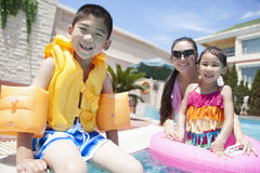 Family portrait, mother, daughter, and son, by the pool with pool toys Royalty Free Stock Photos