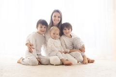 Family portrait of mother and her three boys, isolated on white, back light. From the window behind royalty free stock photography