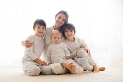 Family portrait of mother and her three boys, on white stock photography