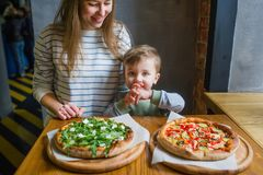 A family portrait of mother and little child eating pizza in restaurant. A family portrait of mother and cute little child eating pizza in restaurant royalty free stock photo