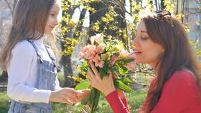 Family portrait in the park during spring sunny day. Young mother receives a bouquet of colorful flowers from her little. Blond daughter, HD stock video footage