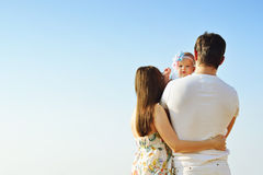 Family portrait. Picture of happy loving father, mother and their baby outdoors. Back view. Family portrait. Picture of happy loving father, mother and their Royalty Free Stock Photos