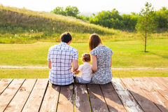 Family portrait. Picture of happy loving father, mother and their baby outdoors. Daddy, mom and child against green hill. Back view stock photos