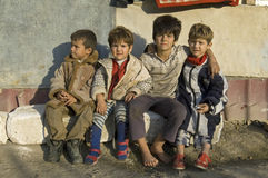 Family Portrait of poor Roma Gypsies, Romania. Romania: in the provincial capital city of Bacau, Group portrait of Roma Gypsies, four children, boys, sitting Royalty Free Stock Photography