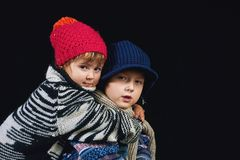 Family portrait , sister hugging big brother . The children are dressed in warm sweaters and fashion knitted hats Stock Image