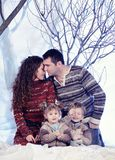 Family portrait sits on studio snow forest background Royalty Free Stock Photography