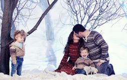 Family portrait sits on studio snow forest background Royalty Free Stock Images