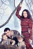 Family portrait sits on studio snow forest background Stock Photo