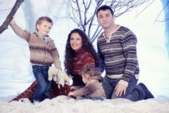 Family portrait sits on studio snow forest background Stock Photography
