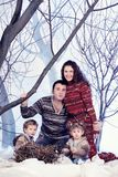 Family portrait sits on studio snow forest background Stock Photos