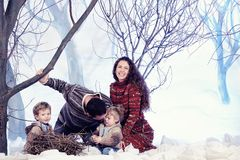 Family portrait sits on studio snow forest background Royalty Free Stock Image