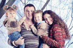 Family portrait standing on studio snow forest background Stock Photo