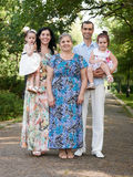 Family portrait in summer city park, parents with child and grandmother, summer season, green grass and trees Stock Images
