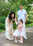 Family portrait in summer city park, parents with child, summer season, green grass and trees Stock Photos