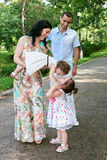 Family portrait in summer city park, parents with child, summer season, green grass and trees Royalty Free Stock Photo