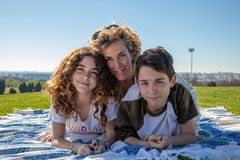 Family portrait on a sunny day with a very loving attitude. Family made up of a mother, son and daughter pose on a sunny day in a public park with a very royalty free stock photo