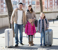 Family portrait of travellers with wheeled trollers in spring da Stock Images