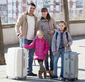 Family portrait of travellers with wheeled trollers in spring da Royalty Free Stock Images