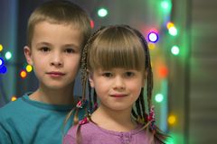 Family portrait of two young happy cute blond children, handsome boy and girl with lot of long braids, brother and sister smiling. Shyly together on colorful royalty free stock photo