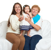 Family portrait on white background, happy people sit on sofa. Children with mother and grandmother Royalty Free Stock Photos