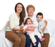 Family portrait on white background, happy people sit on sofa. Children with mother and grandmother Stock Image