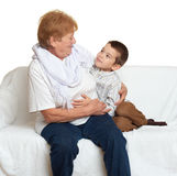 Family portrait on white background, happy people sit on sofa. Grandmother with grandchild. Stock Images