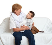 Family portrait on white background, happy people sit on sofa. Grandmother with grandchild. Stock Image