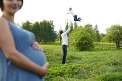 Family. Family Portrait. Young happy Family walking outdoor. Pregnant woman, husband and Child. Dad throws his son up in royalty free stock photos