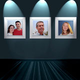 Family portraits on wall. Happy smiling family portraits mounted on wall, illuminated by spotlights Stock Photo