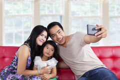 Family posing on camera phone Stock Photo