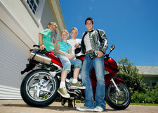 Family posing beside red motorbike on driveway, smiling, side view, portrait (surface level) Stock Photography