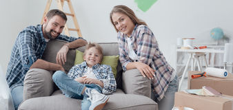 Family posing in their new house. Smiling young loving family posing in their new house, relocation and home improvement concept Stock Images