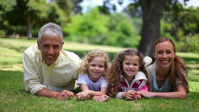 Family posing together while lying on the grass Royalty Free Stock Images