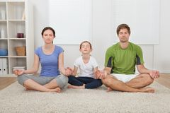 Family practicing yoga at home Royalty Free Stock Photos