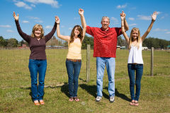Family Praise & Joy. Beautiful family outdoors on their farm holding hands and raising their arms in praise and joy Stock Photo