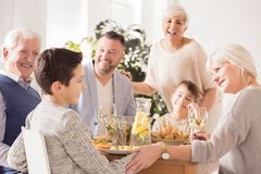 Family praising boy. Happy family praising and congratulating boy at the dinner Royalty Free Stock Photo
