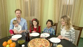 Family praying at dinner table. People with closed eyes. Thank god for food stock video