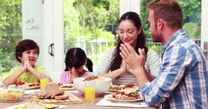 Family praying before eating lunch stock footage
