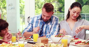 Family praying before eating lunch stock video footage