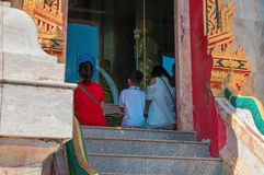 Family is praying on his knees before the Shrine in a Buddhist temple. Rear view. Royalty Free Stock Images
